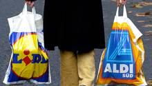 Ein Mann träge Plastiktüten von Lidl und Aldi Süd.