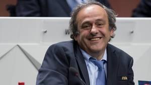 Michel Platini im Anzug an einem Rednerpult