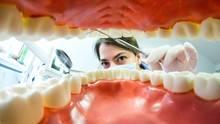 Eine Zahnärztin untersucht einen Patienten