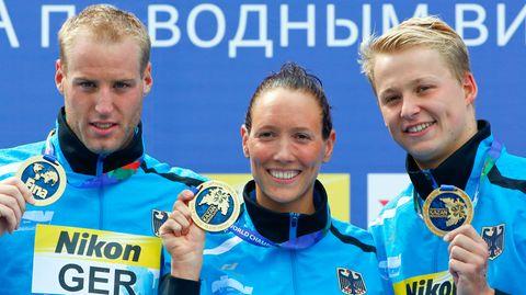 Die Freiwasser-Schwimmer Christian Reichert, Isabelle Härle und Rob Muffels zeigen ihre Goldmedaillen