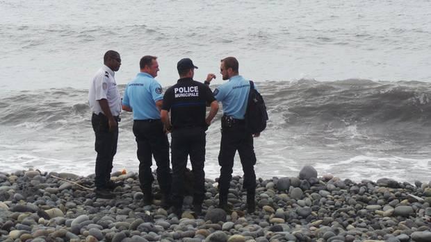 Sicherheitskräfte stehen an dem Strandabschnitt auf derInsel La Réunion, an dem das Wrackteil und der Koffer gefunden wurden