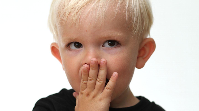 Ein kleiner Junge hält sich überrascht die Hand vor den Mund