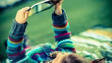 Ein Mädchen liegt auf einer Wiese und spielt mit einem Tablet