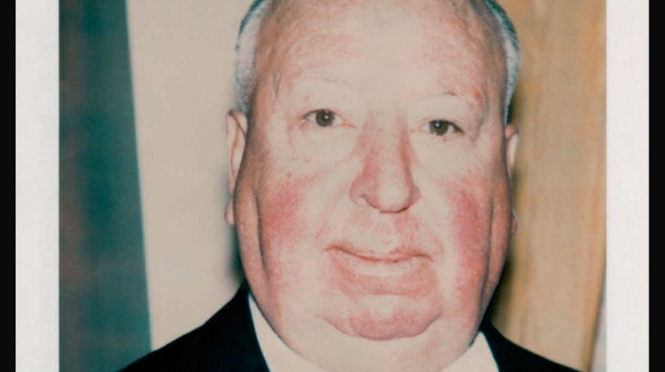 Alfred Hitchcock in Anzug und Krawatte vor unebenem Hintergrund.