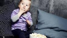 Kleines Kind isst Popcorn und schaut einen Film