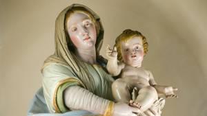 Ein hölzernes Jesuskind liegt im Arm einer Madonnenfigur