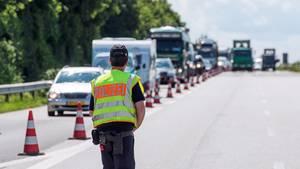 Ein Polizist kontrolliert auf einer Autobahn