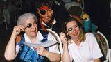 Zwei Damen halten sich einen Löffel vor ihr linkes Auge