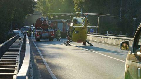 Einsatzkräfte stehen auf einer Brücke über der Isar.