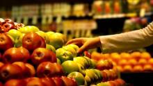 Eine Hand rgeift im Supermarkt zu einem Apfel.