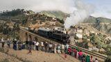 Der Zug bei der Überfahrt der Brücke in Arbaroba, Eritrea am 06.12.2014. Im Vordergrund stehen Teilnehmer der Reisegruppe und fotografieren den Zug.