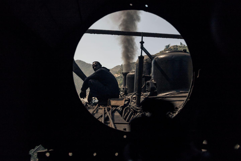 Der Zug macht am 06.12.2014 in Arbaroba, Eritrea Halt, um Wasser aufzunehmen. Blick aus dem Führerhaus während ein Lokführer auf der Lok sitzt.