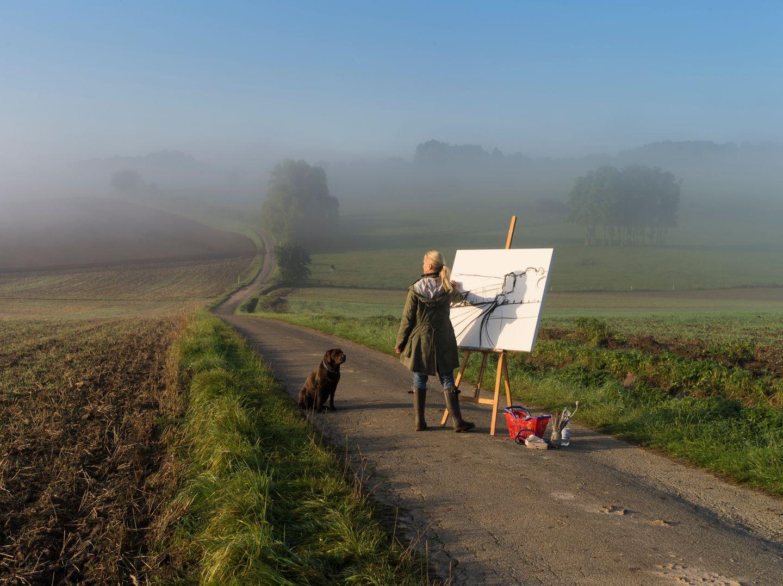"""Reportage """"Vom Glück, allein zu sein"""": am 28.08.2014 steht Stephanie Martschinkebei Sonnenaufgang in der Landschaftbei Bad Driburg-Heerste und zeichnet."""
