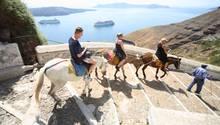 Touristen reiten auf der griechischen Insel Santorin auf Eseln