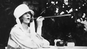 Die altmodische Kopfbekleidung deutet es an: Die goldenen Jahre des Zigarettenhalters liegen lange zurück.