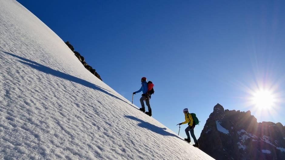 Zwei Bergsteiger mit Eispickel im Aufstieg