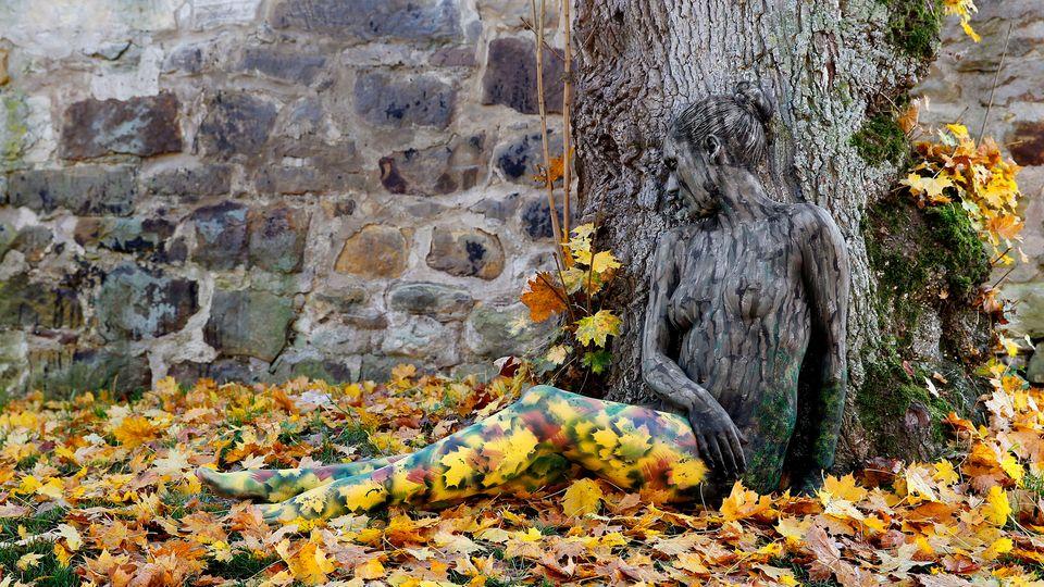 Frau sitzt mit Bodypainting kaum sichtbar im Laub, angelehnt an einen Baum