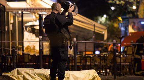 Ein Polizist steht neben einer zugedeckten Leiche am Boulevard Voltaire in Paris