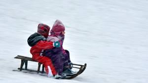 Kinder fahren mit einem Schlitten einen Berg hinab