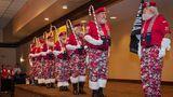"""Das """"Santa drill team"""" präsentiert sich auf der Bühne. Anstelle von Gewehren tragen die Weihnachtsmänner riesige Zuckerstangen."""