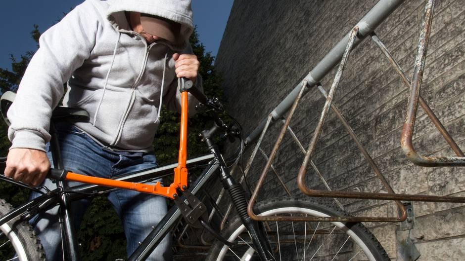Ein Mann knackt mit einem Seitenschneider ein Fahrradschloss