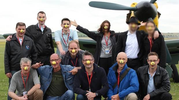 """Die internationale Community der virtuellen Flieger trifft sich regelmäßig auf Airshows wie hier im britischen Duxford 2016. Man erkennt sich am """"Vereinsshirt"""". Diese Gruppe trägt zum Spaß gelbe Nasen - wie die im Hintergrund stehende Messerschmitt 109 einst in der Luftschlacht um England."""