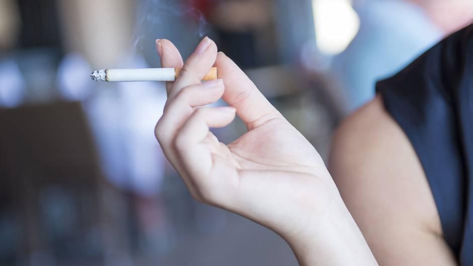 Eine Frau hält eine Zigarette in der Hand