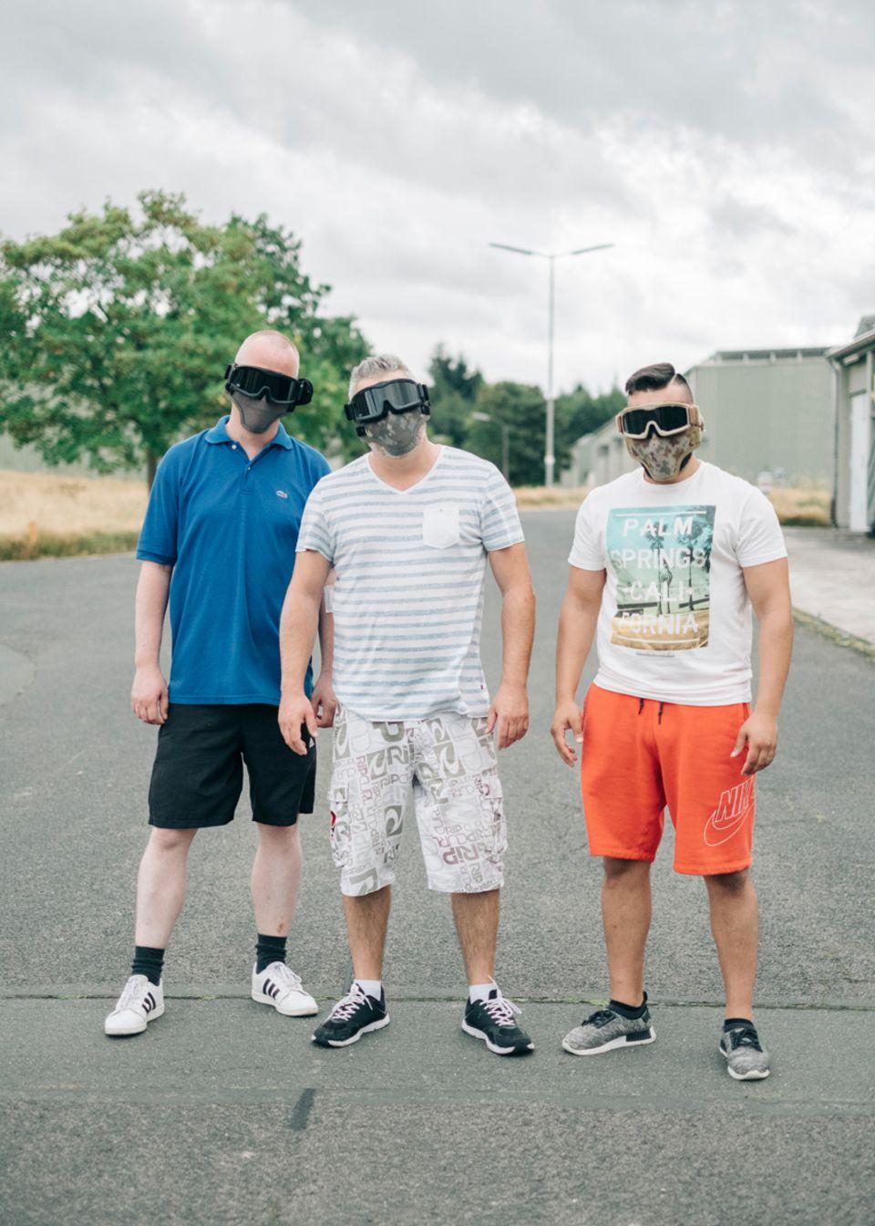 Politik: Werden gleich beschossen: links Stephan, rechts Tolga, in der Mitte ihr Chef Herr Huber. Die Masken sollen sie vor den Softairpatronen schützen.