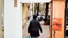 Eine Frau geht mit einer Plastiktüte an einer Hausfassade entlang. Franziska Giffey spricht über das Regieren in Neukölln.