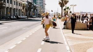 Ist Arbeit verlorene Zeit? Eine junge Frau fährt auf einer Straße Skatebord, sie hat ein Surfbrett in der Hand.
