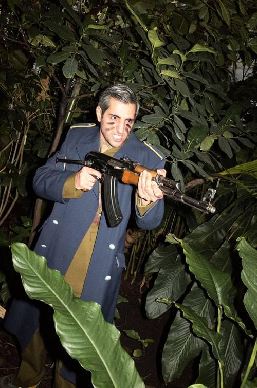 Michel Abdollahi steht in Uniform zwischen großen Grünpflanzen und hält ein Gewehr in der Hand.