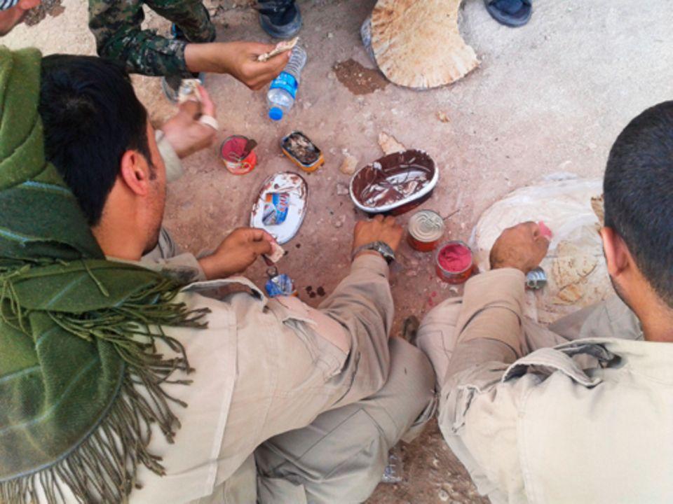 Politik: Waffenruhe: In einer Pause zwischen Gefechten nehmen die Kämpfer im syrischen Ort Suluk eine Mahlzeit ein.