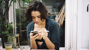 Überwachung total: Eine junge Frau raucht eine Zigarette und tippt auf ihrem Smartphone