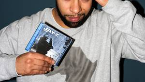 Megaloh hält das Album »The Blueprint« von Jay-Z in der Hand