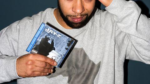 Megaloh hält das Album »The Blueprint« von Jay-Z in der Hand