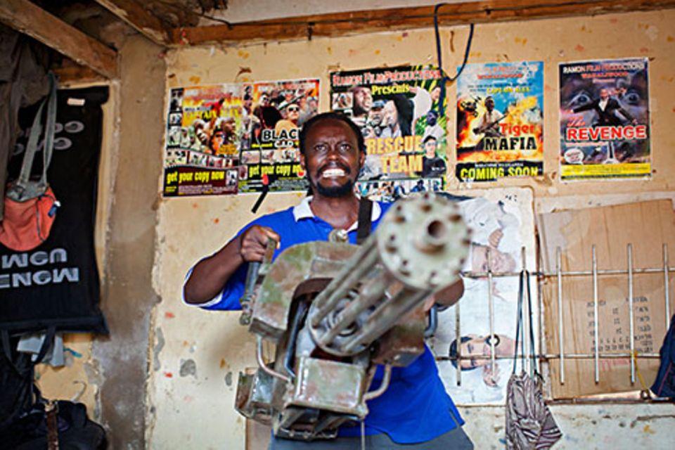 Zuhause: Ein Mann und sein Traum: Isaac vor den Postern seiner beliebtesten Filme. Die Waffe, die er hält, hat Dauda gebaut. Sie hat sogar einen Namen: Maria