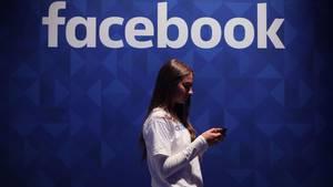 Eine Frau steht mit einem Smartphone vor dem Facebook-Logo