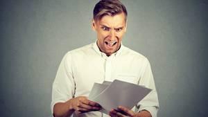 Ein Mann schaut erschrocken eine Rechnung an