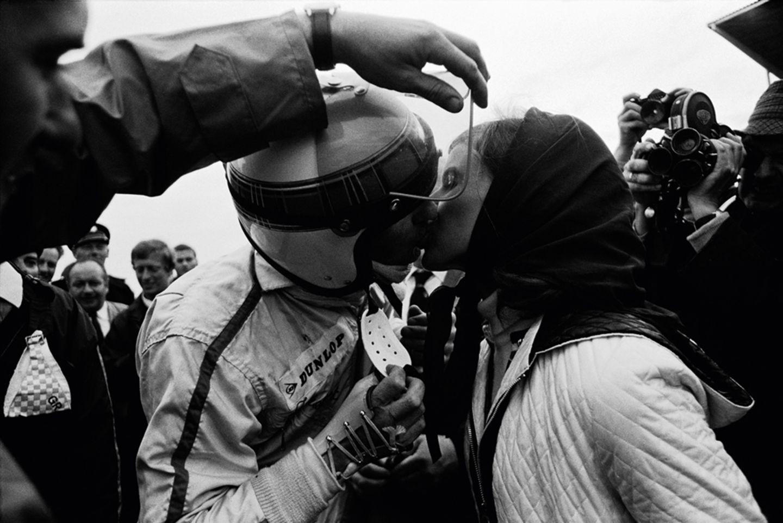 1968 GP Holland: Nach dem Sieg in Zandvoort küssen sich die Stewarts. Ein Helfer muss das Visier öffnen, denn die rechte Hand des Piloten ist stark bandagiert.  The Golden Age of Formula 1, Kleine Ausgabe - Rainer W. Schlegelmilch - 24,90 Euro