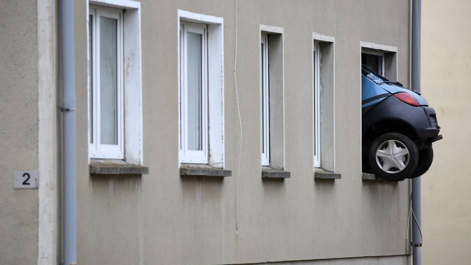 Das Heck eines Kleinwagens ragt aus dem Fenster eines Mehrfamilienhauses in Kummer