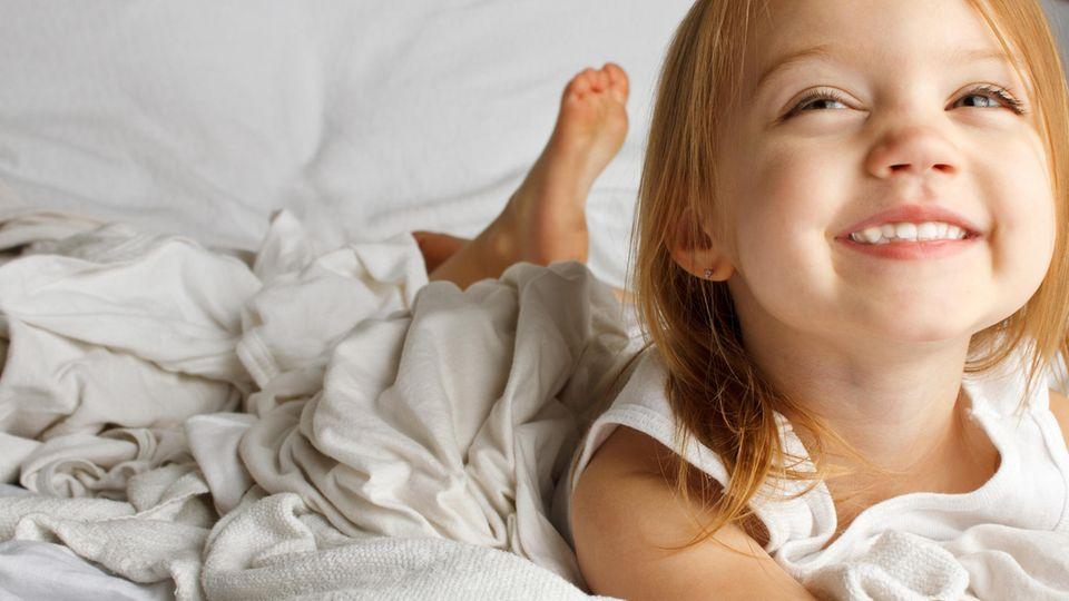 Mädchen liegt im Bett und grinst