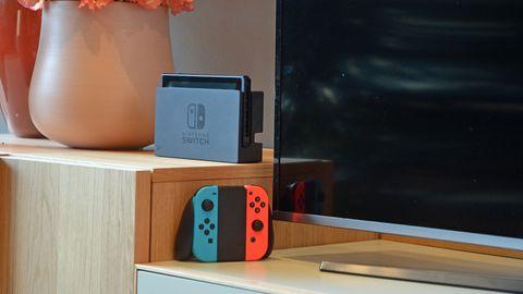 Die Nintendo Switch steht im Dock vor einem Fernseher, daneben die JoyCons in ihrer Halterung