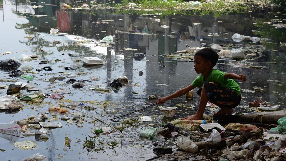 Ein Junge in Kambodscha spielt an einer verdreckten Wasserfläche. Die WHO sieht dringenden Handlungsbedarf.