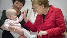 Angela Merkel auf einem Pressetermin mit einem Baby