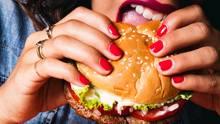 Eine Frau beißt in den Impossible Burger.