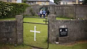 Massengrab für 800 Babys im irischen Tuam: Grüner Rasen, umgeben von einer Mauer mit einem Tor mit weißem Kreuz