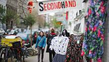 Eine Frau geht an einem Second-Hand-Shop vorbei.