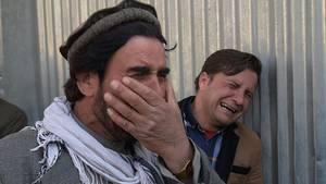 Zwei afghanische Männer trauern um ihre Angehörigen