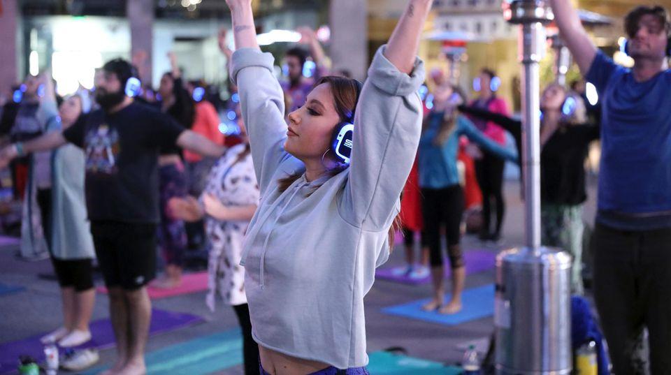 Eine Yogalehrerin vor den Kursteilnehmern. Alle strecken die Arme in die Luft.