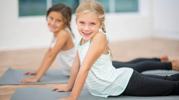 Zwei Mädchen in Turnzeug auf Yogamatten
